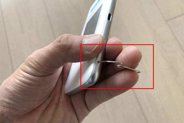 左下にあるリセットボタン(小さい穴)にクリップなどを挿して5秒間待つ。